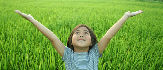 Girl standing in tall green grass with upward raised hands